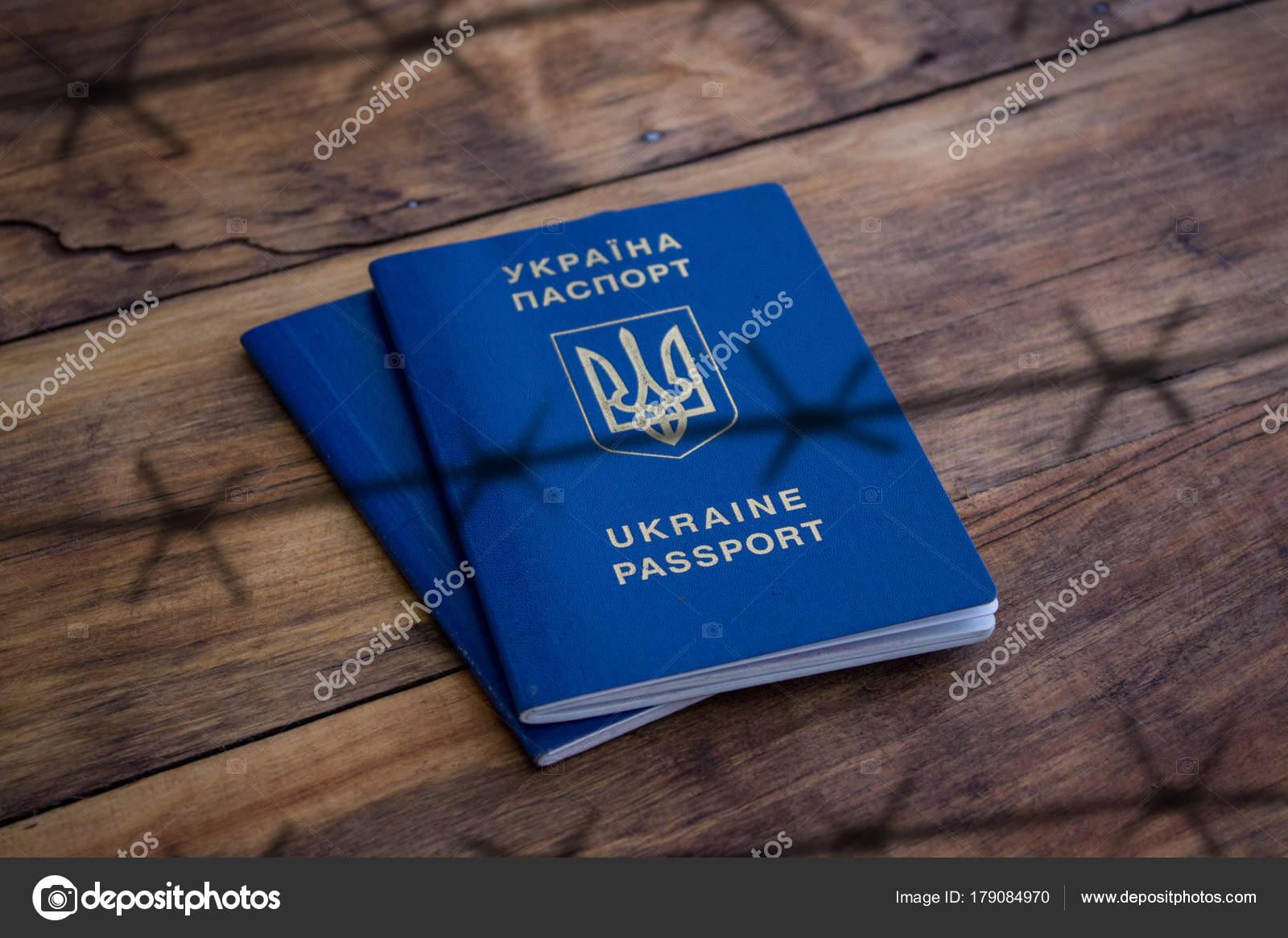Ukrainischen Pass hinter Stacheldraht auf einer hölzernen Textil-ba ...