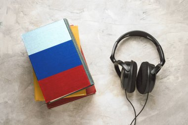 Headphones and a pile of books. The upper book has a cover in th