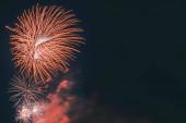 Gyönyörű ünnepi vörös tűzijáték füsttel a sötét égen egy ünnepség alatt fénymásolás helyet. Karácsony, Szilveszter, Függetlenség napja, Valentin-nap, születésnapi üdvözlőkártya koncepció.