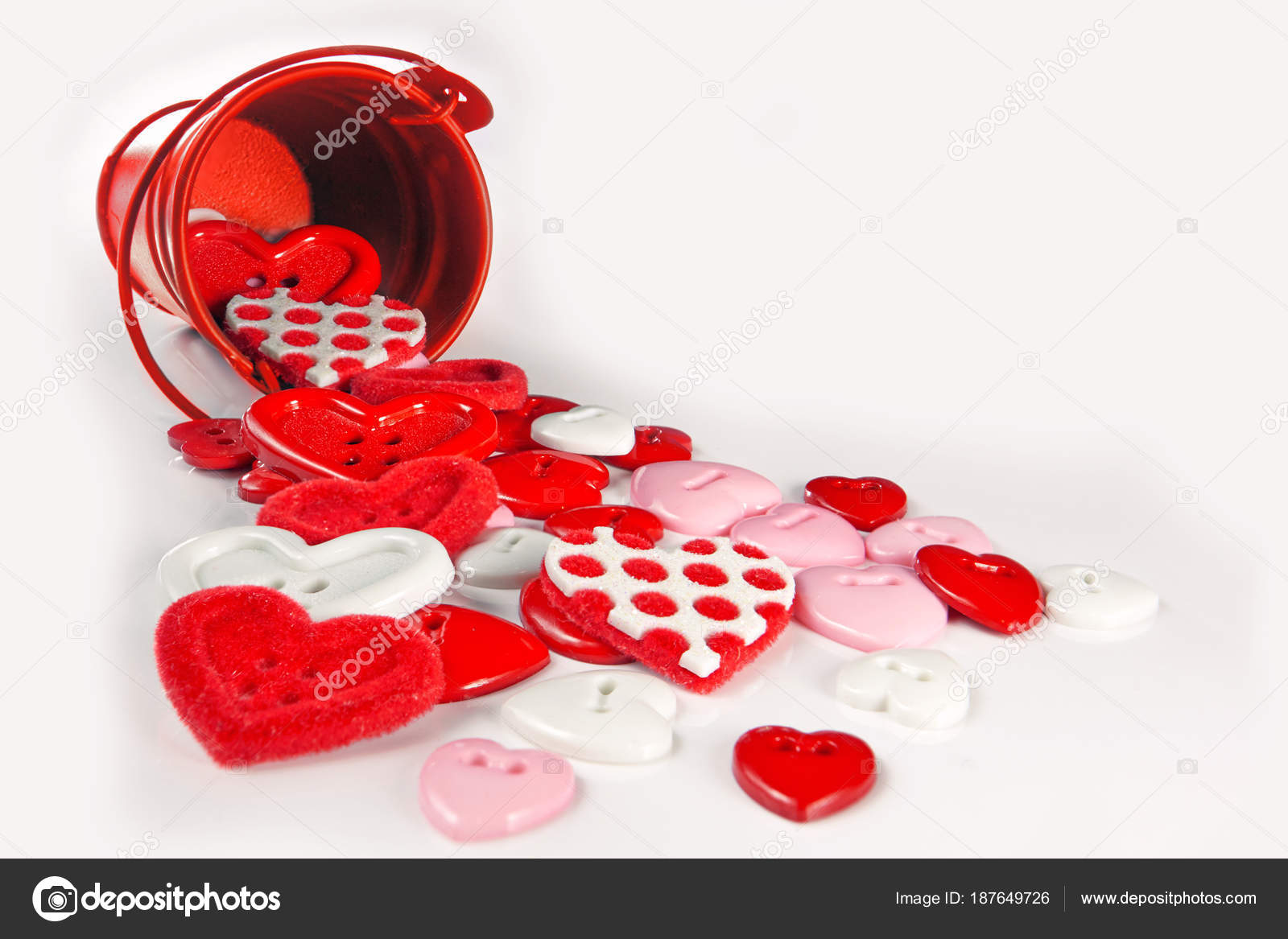 Red hearts buttons spill out of the bucket  The concept of