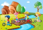 Děti jezdit na kole přes most