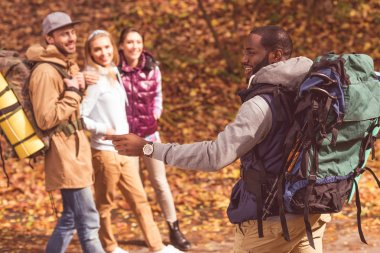 Smiling man with friends in autumn forest