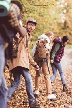 Friends backpackers in autumn forest
