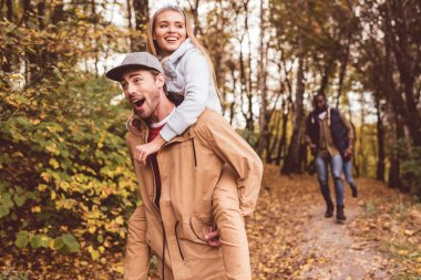 Happy young couple piggybacking in forest