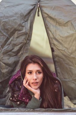 Woman laying in opened tent