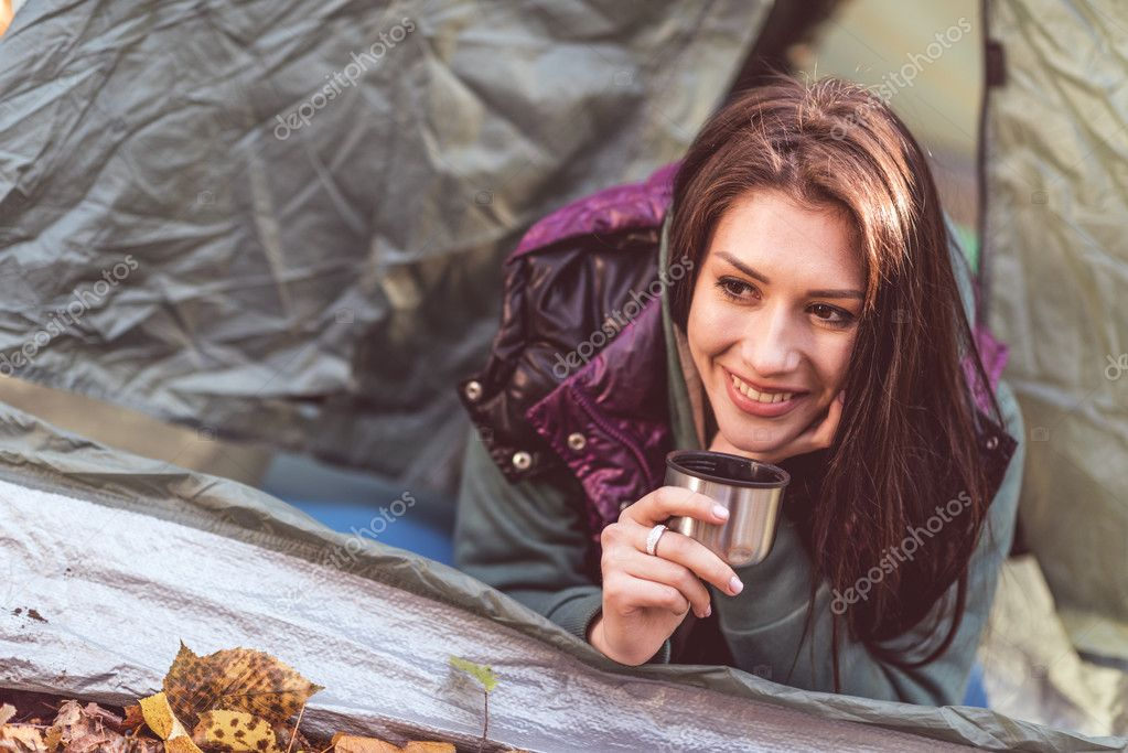 Woman in tent holding metallic cup