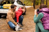 Fotografie Happy family playing with dog in forest