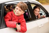 Lächelnder Junge, der durch das Autofenster schaut