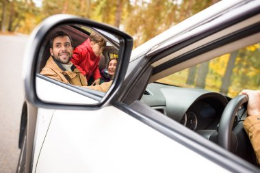 Happy family reflected in car mirror