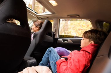 Smiling boy in back seat of car