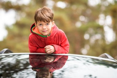 Cute little boy standing in car