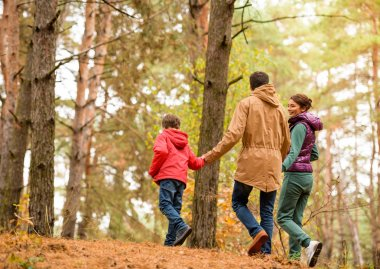 Family walking in autumn forest