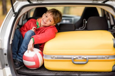 Smiling little boy sitting in open car trunk with ball and baggage stock vector