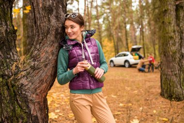 Smiling woman with thermos in autumn forest