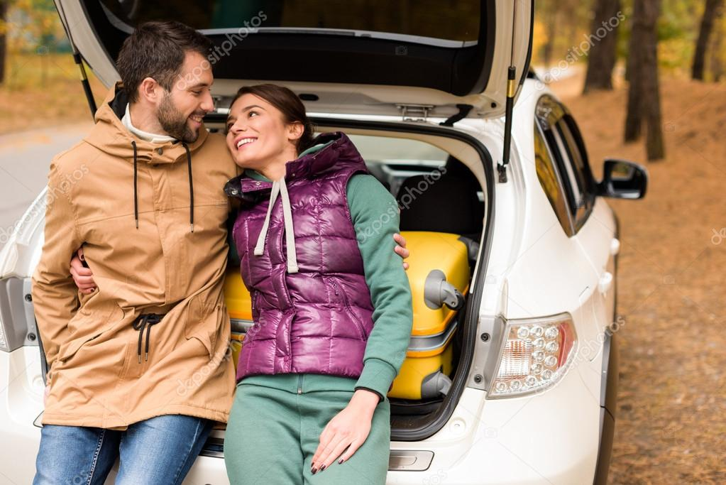 Smiling couple sitting in car trunk