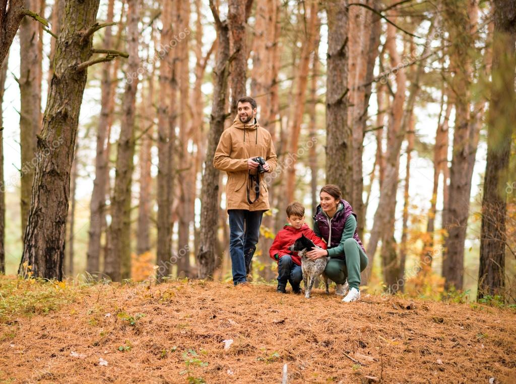 Woman and boy playing with dog in forest