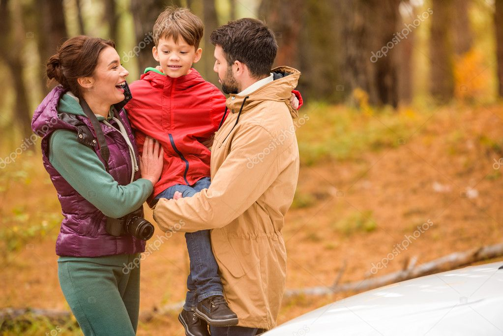 Happy family near car in forest