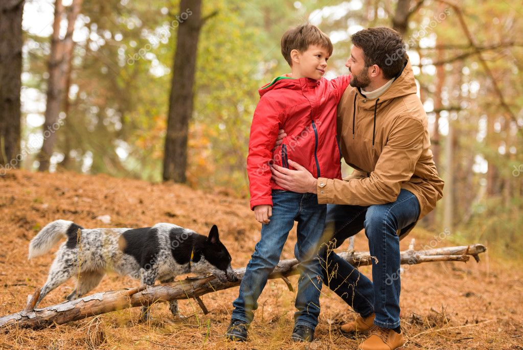 Happy boy playing with father and dog