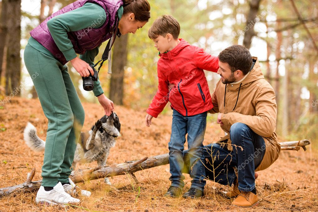 Happy family with dog in forest