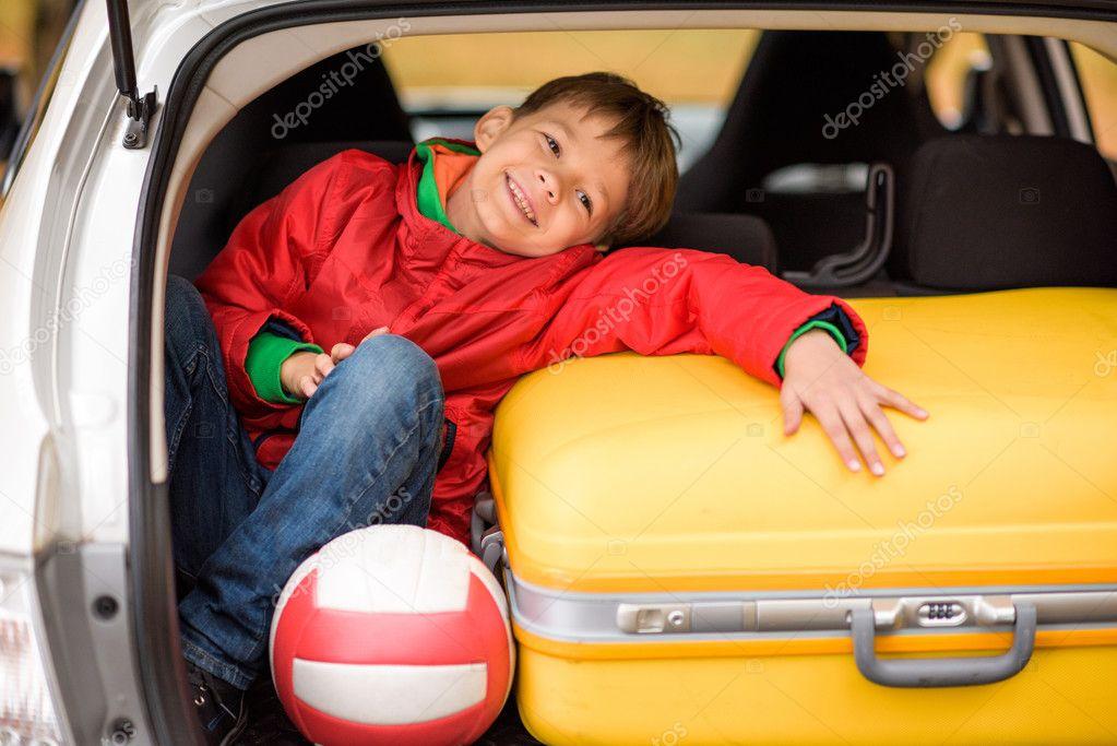 Smiling boy sitting in car trunk