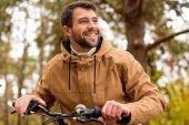 Photo Smiling man sitting on bicycle