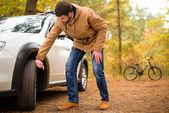 Mann überprüfen Pkw-Reifen