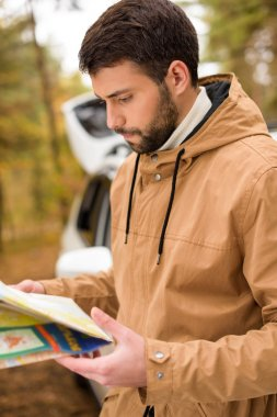Bearded man holding map in forest