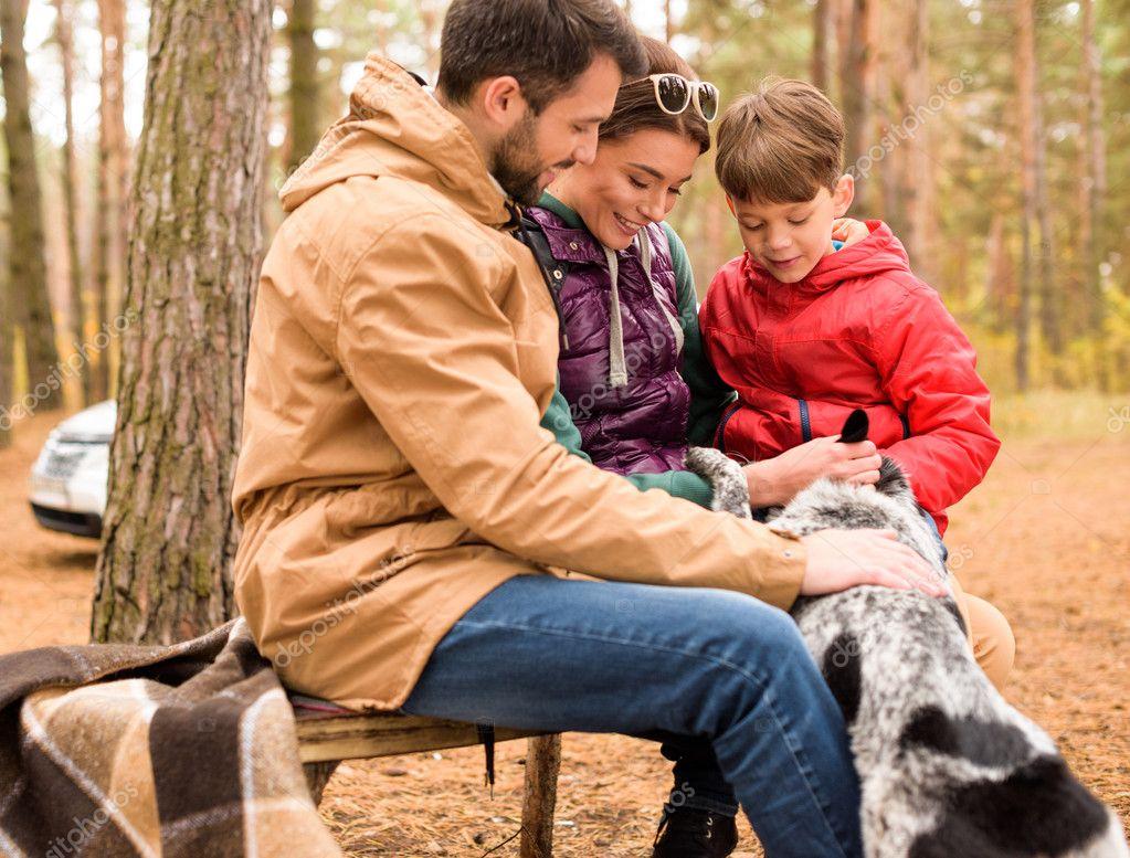 Happy family stroking dog