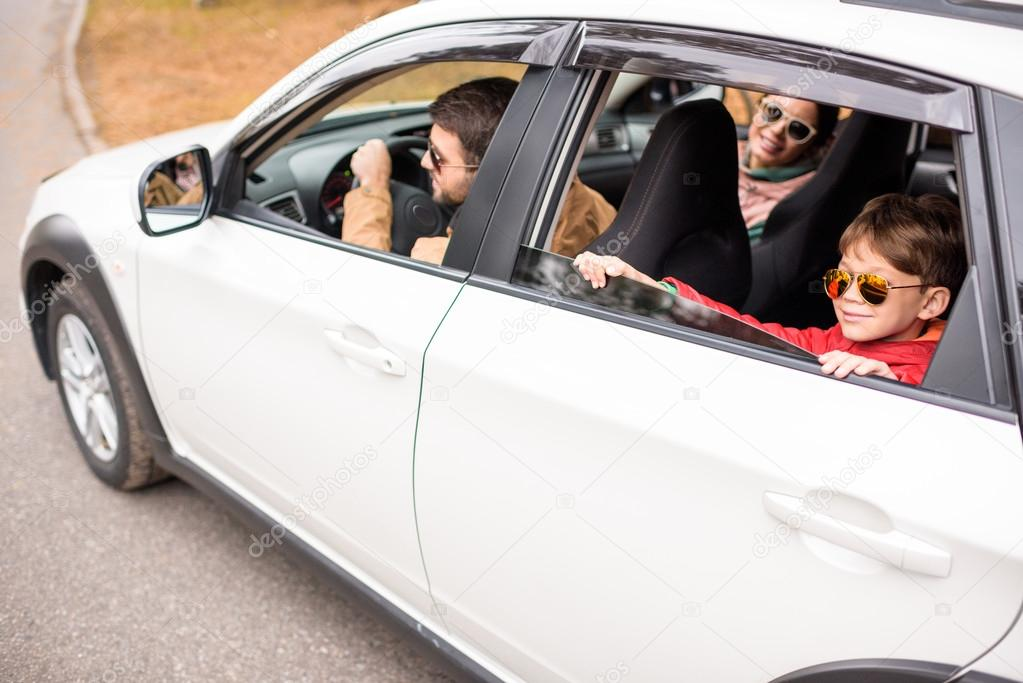 Happy family travelling by car