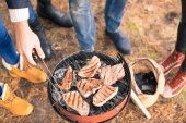 Fotografie Lidé vaření masa na gril na dřevěné uhlí