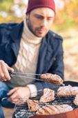 Muž vaření masa na gril na dřevěné uhlí