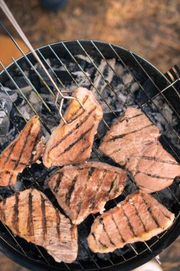Grilling meat on charcoal grill