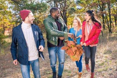 Happy friends walking in autumn park