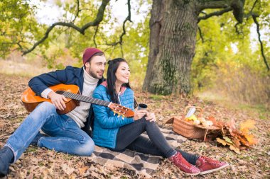 Happy romantic couple sitting on plaid and enjoying guitar in autumn forest stock vector