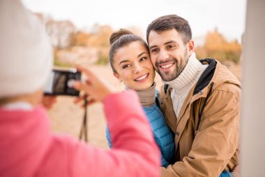 Girl photographing beautiful smiling couple