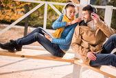 Fotografie Mladý pár sedící na lavičce v sluchátka
