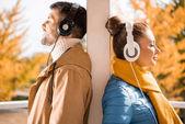 Mladý muž a žena stojící v sluchátka
