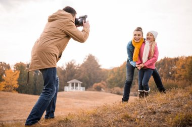 Young man photographing happy mother and daughter with instant camera outdoors stock vector
