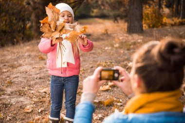 Mother photographing daughter in autumn park