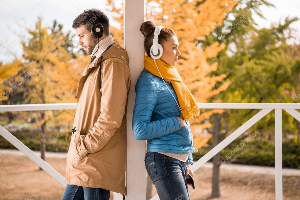 Young man and woman standing in headphones