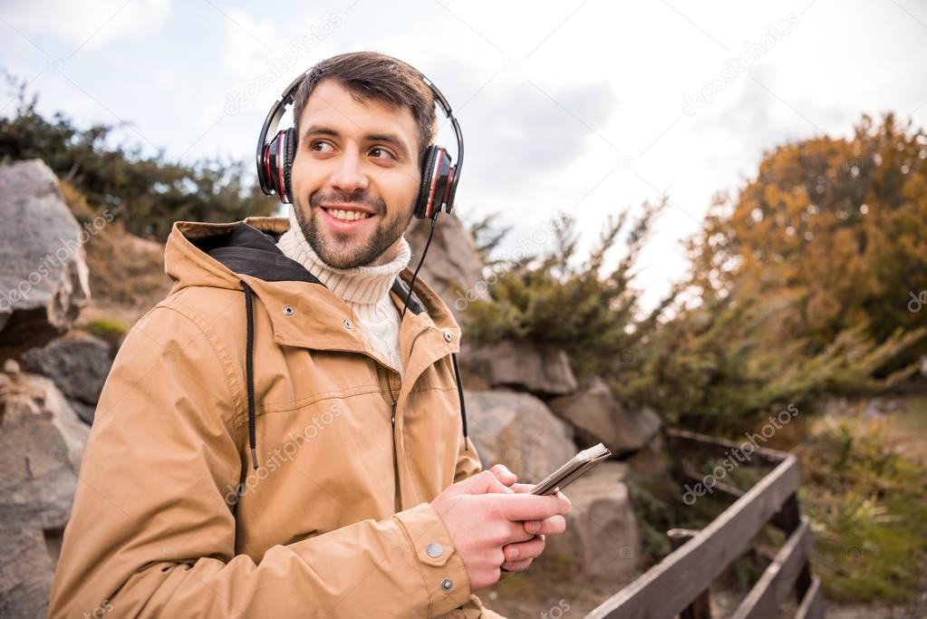 Man in headphones holding smartphone