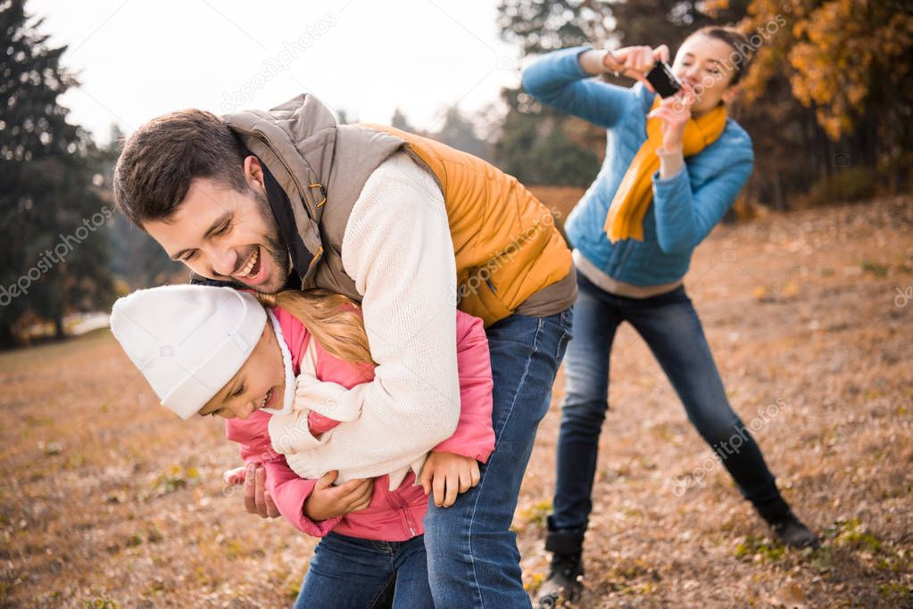 Man playing with little daughter in park