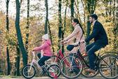 Photo Happy family riding bikes in park