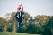 Fotografie Usmívající se otec dcera provozující ramena