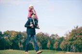 Usmívající se otec dcera provozující ramena