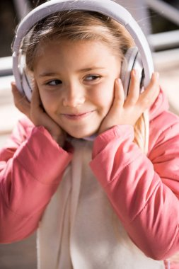 Smiling little girl in white headphones