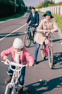 Cheerful family biking in park