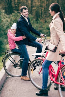 Cheerful family standing with bicycles
