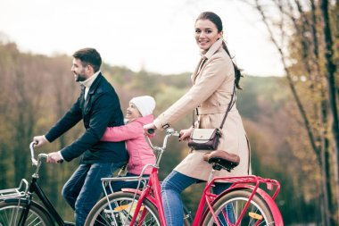 Happy family riding bicycles in park