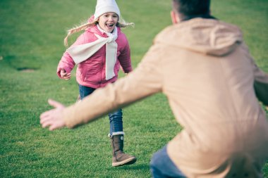 Adorable smiling girl running to father